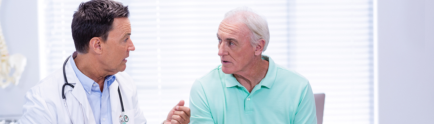 senior man having a conversation with physician in medical office