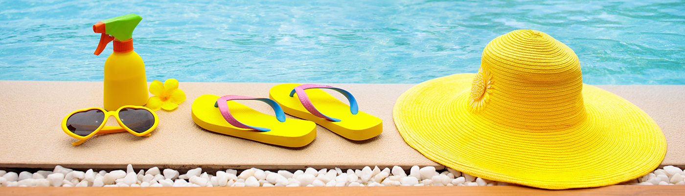 yellow sunglasses, spray bottle, flower, flip-flops and hat sitting on ledge next to pool.