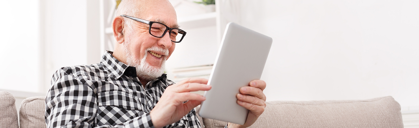 senior man reading a tablet on sofa