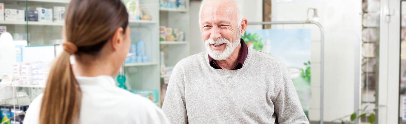 smiling senior man at pharmacy speaking with pharmacist